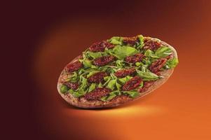 brasiliansk pizza med tomatsås, mozzarella, rucola, torkade tomater och oregano i en leveranslåda foto
