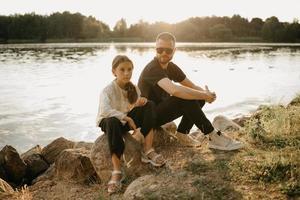 en ung far med skägg och solglasögon poserar med sin vackra dotter vid kusten foto