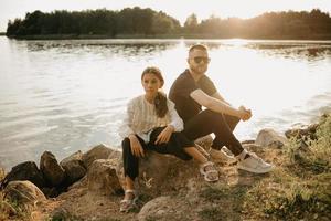 en ung far med skägg och solglasögon poserar på stenar med sin dotter vid kusten foto