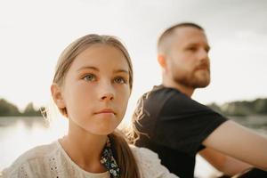en ung far med skägg sitter med sin dotter vid sjön foto