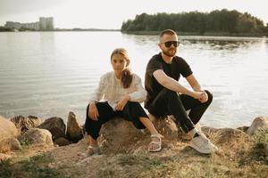 en ung far med skägg och solglasögon sitter på stenar med sin dotter vid kusten foto