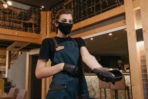 en servitris som bär ett förkläde, en svart medicinsk ansiktsmask och medicinska handskar för engångsbruk har en trådlös betalterminal i en restaurang