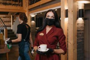 en kvinnlig restaurangchef bär en svart ansiktsmask och engångshandskar som håller en kopp kaffe i en restaurang foto