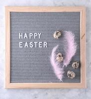 skylt med text glad påsk, rosa fjädrar och ägg foto