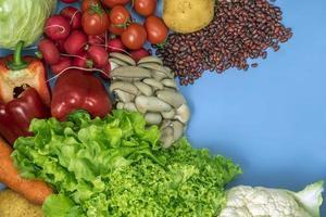produkter för en vegetarisk detoxdiet av blomkål, sallad, rädisor, tomater, svamp, bönor och röd paprika på blå bakgrund foto