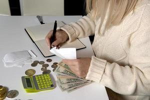 närbild av en kvinna som beräknar pengar och skriver i en anteckningsbok