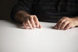 oigenkännlig man i en bekant position som sitter vid ett vitt tomt bord