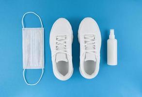 vit medicinsk mask, tränare och handdesinfektionsmedel på en blå bakgrund, svartvitt platt karantändräkt foto