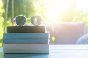 böcker på ett bord med solglasögon på toppen i ett semesterrum på semester, läsning och avkopplande terapi utbildning koncept foto