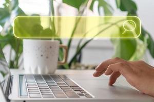 en hand som använder en bärbar dator som söker efter information på internet med en sökruta-ikon foto