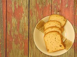 skivat bröd på en keramisk tallrik på en träbordbakgrund foto