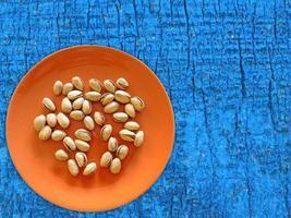 pistaschmandlar på en orange tallrik på ett träbord bakgrund foto
