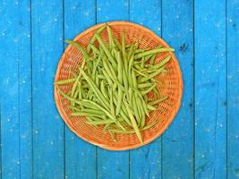 gröna bönor på en korgplatta på ett träbord bakgrund foto