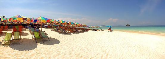 panorama av färgglada paraplyer och fåtöljer på stranden foto
