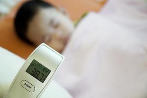 sjukt barn med termometer som visar feber foto