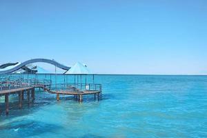 azurblått vatten med pir under blå himmel