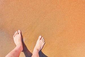 mans fötter på stranden foto