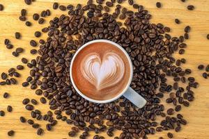 ovanifrån av en mugg kaffe med bönor på träbakgrund. foto