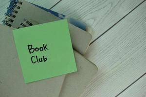 bokklubben skriven på ett anteckningsblock isolerad på träbord foto