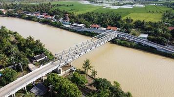 bekasi, indonesien 2021- Flygfoto över en lång bro vid slutet av floden som förbinder två byar foto
