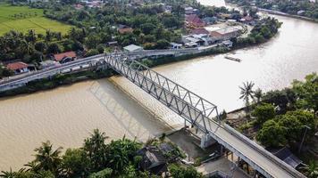 bekasi, Indonesien 2021 - Flygfoto över en lång bro till slutet av floden som förbinder två byar foto