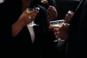 människor i snygga kostymer som håller glas champagne foto