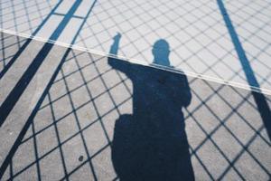 mans skugga med ett repnät på marken foto