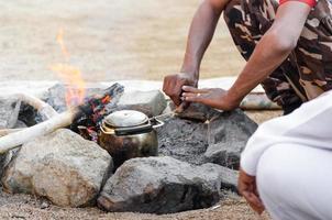 människor värmer en tekanna i en eld foto