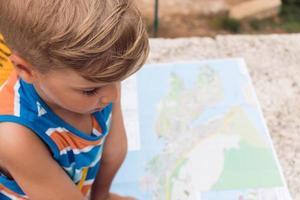 liten pojke söker riktning på kartan foto