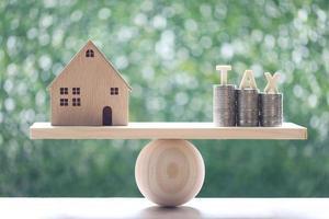 modellhus med stapel mynt och skatteord på gungbräda grön bakgrund foto