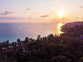 Flygfoto över den vackra stranden och havet med kokospalmen vid solnedgången