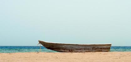 gammal båt på sanden mot havet foto