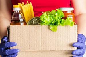person som håller en låda med matvaror foto