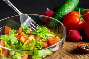 säsongsbetonad sommargrönsaksallad i en glasskål foto
