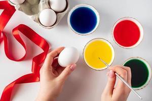 ung kvinna som målar vita ägg till påsk foto