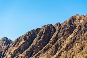 toppar av steniga berg mot en blå himmel i Egypten foto