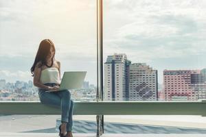 kvinna som använder en bärbar dator med stadsbilden bakgrund