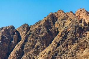 steniga bergstoppar och blå himmel foto