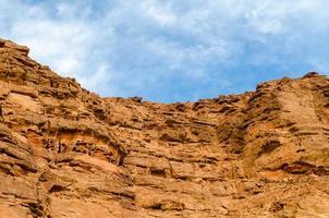 blå himmel över ett stenigt kanjon ansikte foto