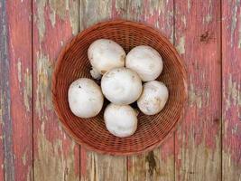 vita svampar på en korgplatta på en träbordbakgrund foto