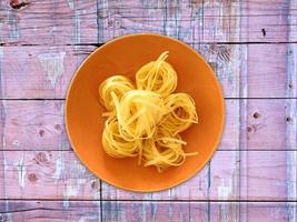 pasta på en orange tallrik på en träbordbakgrund foto