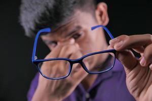 man som håller glasögon i förgrunden