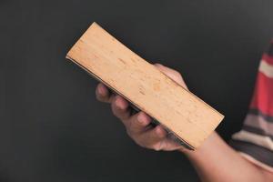 person som håller gammal bok på svart bakgrund foto