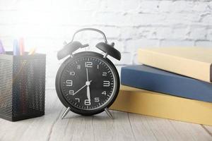 böcker och väckarklocka på skrivbordet foto