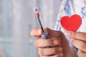 sjuksköterska som håller hjärtat och insulinpenna