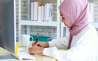 vacker muslimsk affärskvinna som arbetar lyckligt på kontoret foto
