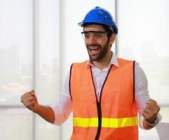 säker man står leende på byggarbetsplatsen