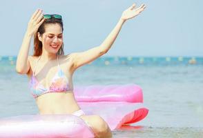 asiatisk kvinna kopplar av på sommarsemester på stranden