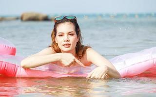 vacker asiatisk kvinna som slappar på stranden lyckligt
