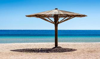trä strandparaply på sanden